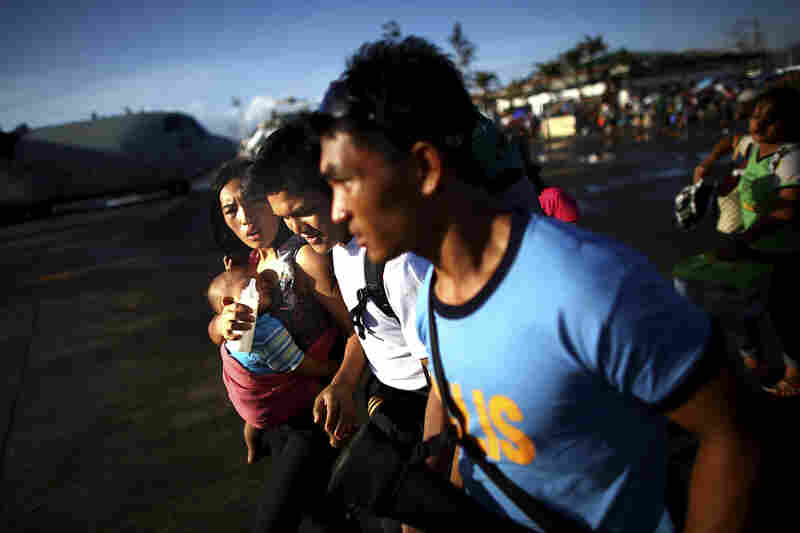 A family runs across the airport tarmac hoping to board an emergency evacuation flight out of the devastated city.