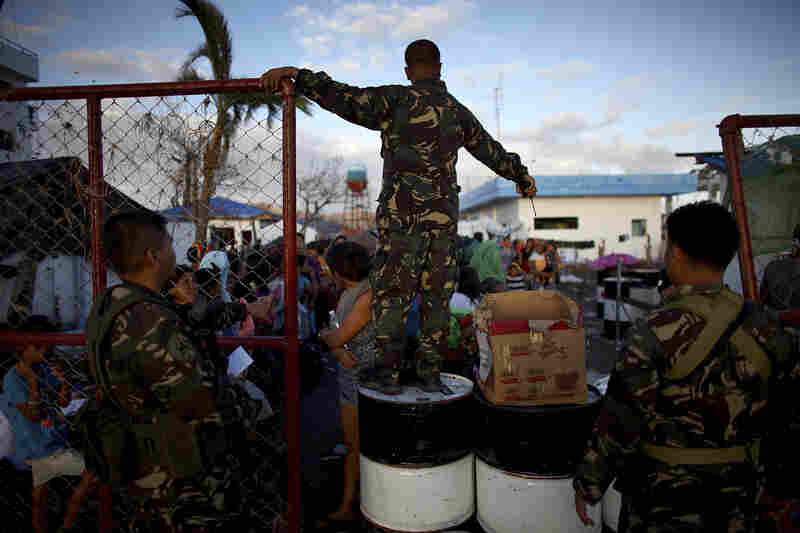 A Filipino soldier stands guard at an airport gate. Thousands of people wait outside in hopes of getting a ride out of the area on the ongoing emergency airlift.