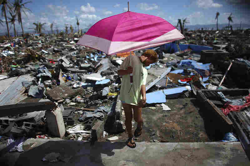 A woman holds a beach umbrella as she walks through a leveled area in San Jose.