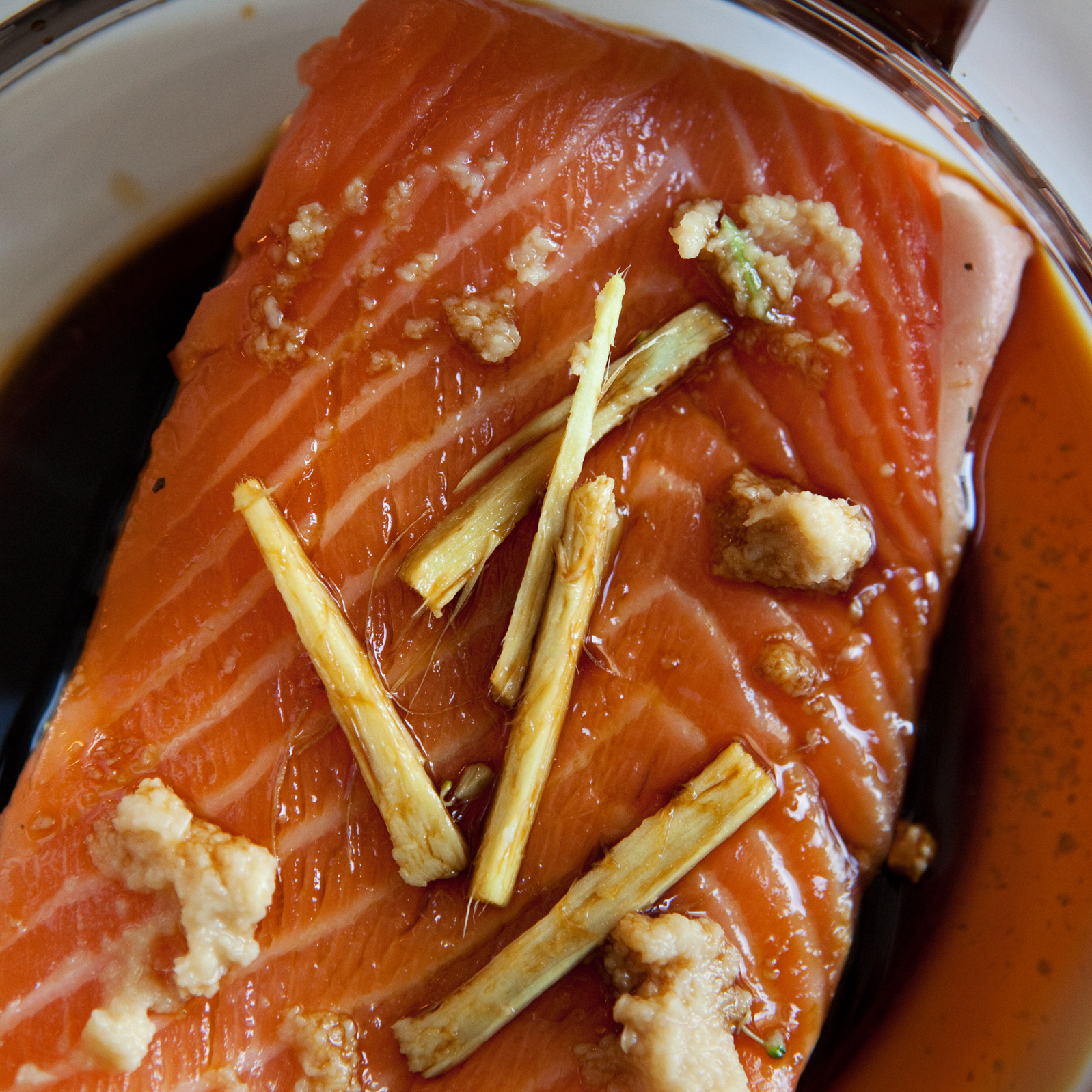 A slice of salmon with ginger, garlic and soy sauce sits in the coffee maker's carafe ready for poaching.