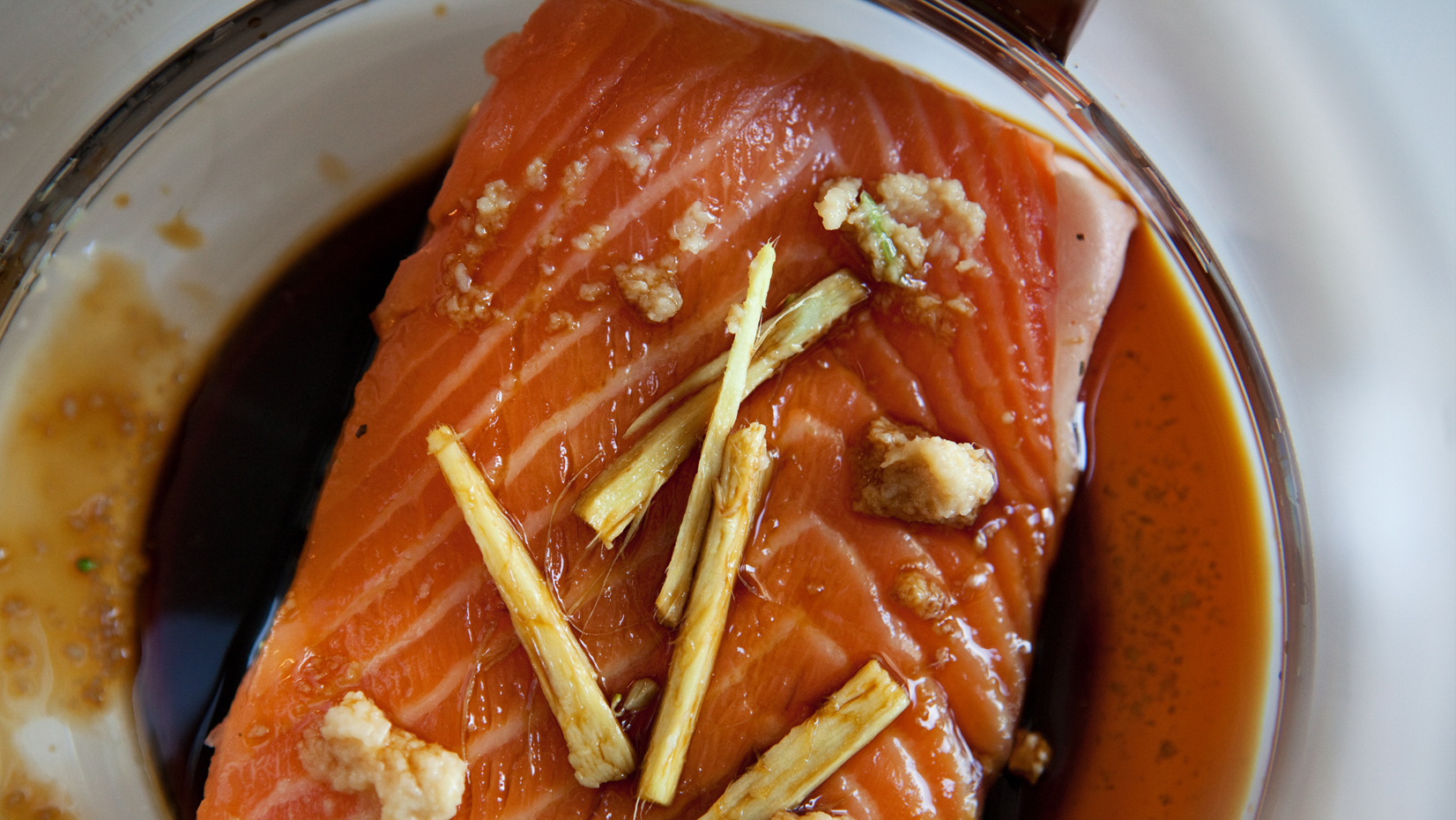 A slice of salmon with ginger, garlic and soy sauce sits in the coffee maker's carafe. Sliced broccoli and cauliflower are steamed in the basket while the salmon poaches below.