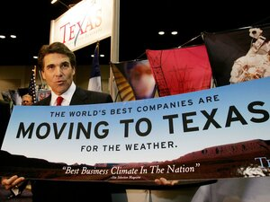 Texas Gov. Rick Perry holds a sign promoting business in Texas, in San Antonio, on Nov. 8, 2004. Nearly a decade later, Perry is still touting the state's pro-business bent, including a tour this summer to several states.