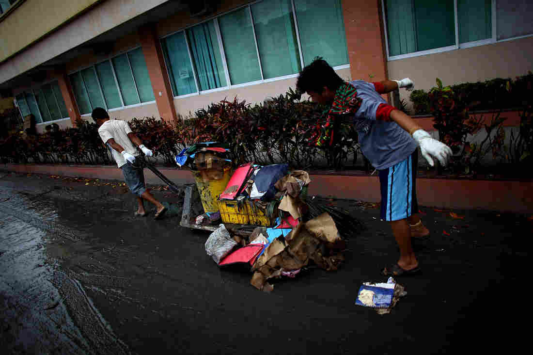 In the courtyard of the Divine Word Hospital, men shovel thick black mud that was left behind by the storm surge.