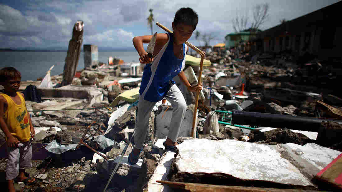 A Filipino boy climbs up a pile of wreckage outside the devastated Eastern Visayas Regional Medical Center in Tacloban on Saturday.
