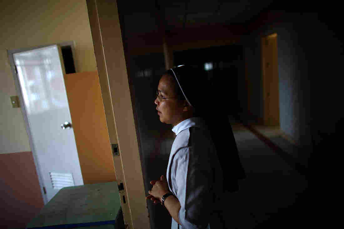 Sister Eliza Arpon checks on the condition of the damaged ward rooms and ER facilities at Divine Word Hospital in Tacloban, Philippines, on Saturday.