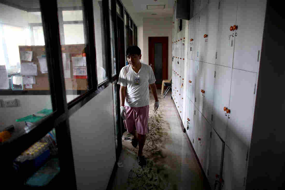 A worker walks through mud and water in the hallways of the Divine Word Hospital in Tacloban, Philippines, on Saturday.