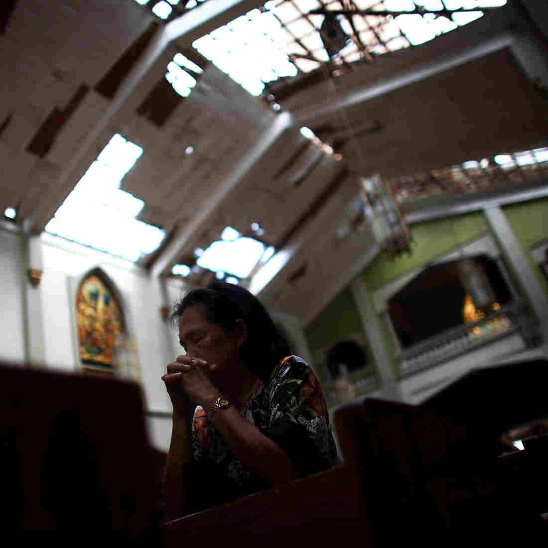 A Filipino woman prays at morning Mass at Santo Nino church, which was damaged by Typhoon Haiyan in Tacloban, Philippines, on Sunday.