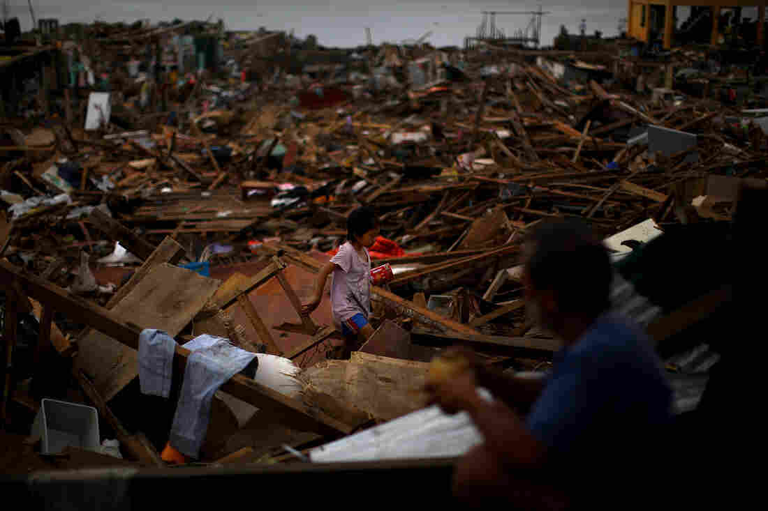 A girl crosses between collapsed roof tops in the damaged downtown area in Tacloban, Philippines, on Sunday.
