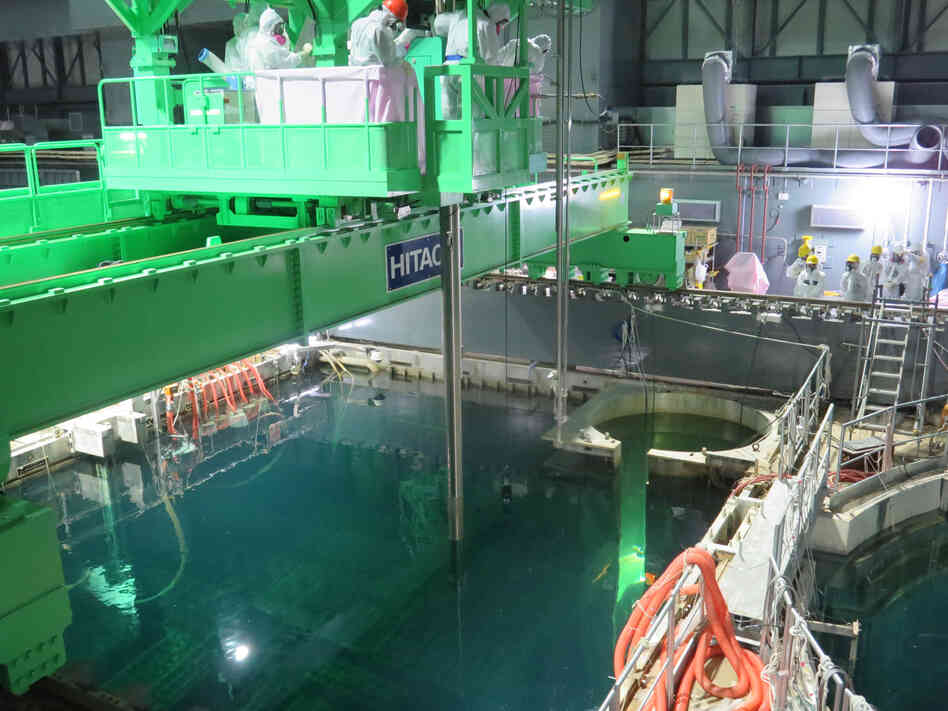 Workers remove nuclear fuel rods from a pool at the Unit 4 reactor of the Fukushima Daii-chi nuclear power plant on Monday.