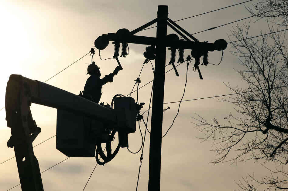 A lineman grounds a line on a replacement pole in McNeill, Miss., after 2012 Christmas day storms downed both telephone and electric power lines and poles throughout the state. Upkeep on traditional landlines is expensive, and some are pushing for relaxing requirements that phone companies maintain these lines.