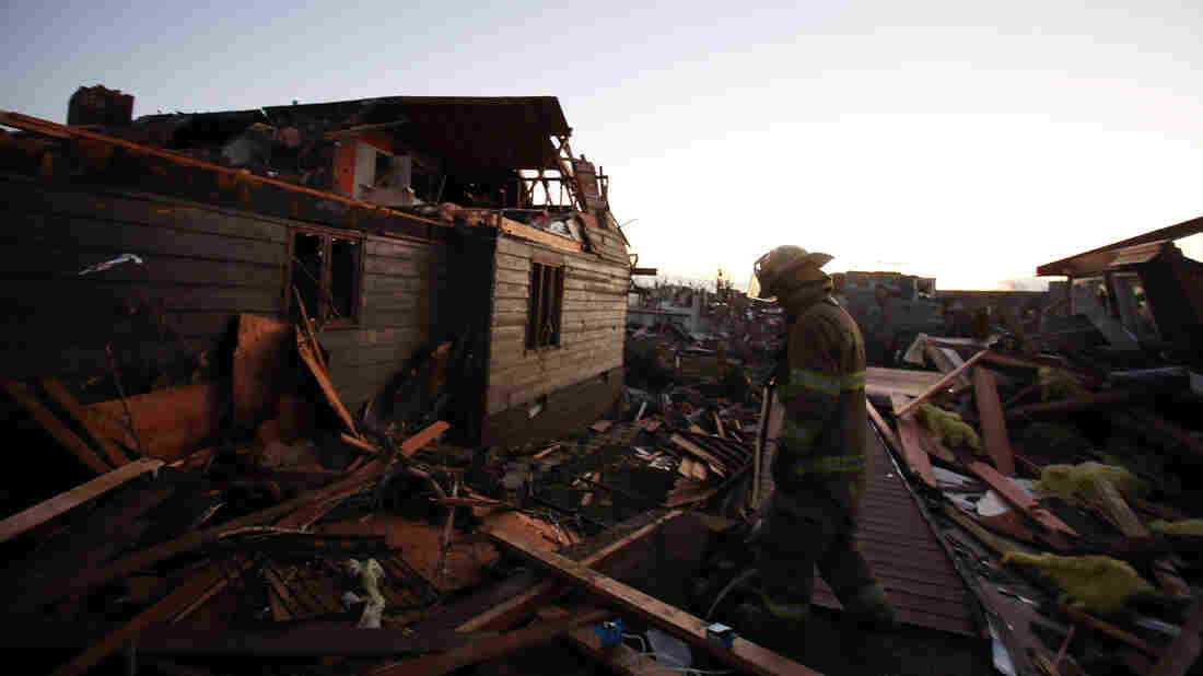 A firefighter searches through debris in Washington, Ill., on Sunday. Tornadoes and severe weather roared through the area earlier in the day.