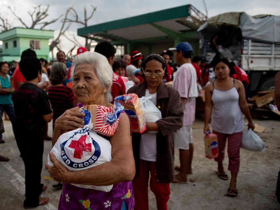 An elderly woman and others leave after getting some help from Red Cross volunteers Monday in Dagami, the Philippines,