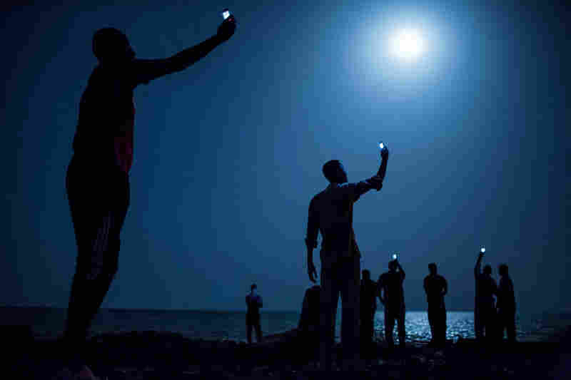 African migrants crowd the night shore of Djibouti city, trying to capture inexpensive cell signals from neighboring Somalia—a tenuous link to relatives abroad. For more than 60,000 years our species has been relying on such intimate social connections to spread across the Earth.