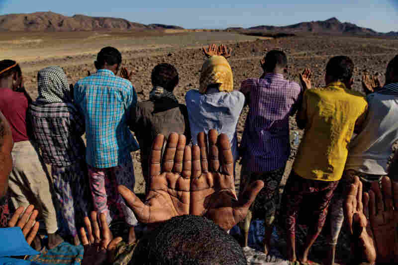 Villagers pray for rain in the Afar desert. A megadrought lasting thousands of years may have bottled up early humans in Africa, making travel risky. A climate shift bringing wet periods likely helped propel the first migration.