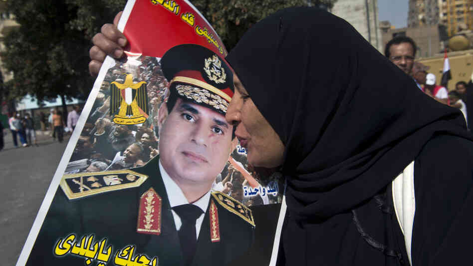 An Egyptian woman kisses a poster of Gen. Abdel-Fattah el-Sissi as she arrives at Cairo's Tahrir Square to mark the 40th anniversary of the 1973 Arab-Israe
