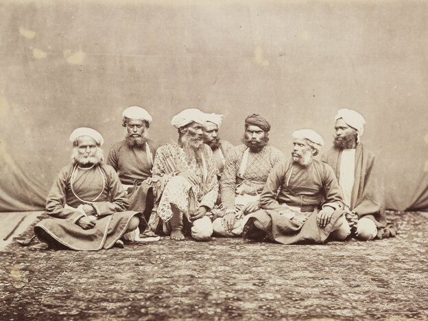 "A photograph of a group of elderly men sitting on a mat, taken in Peshawar, now in Pakistan, circa 1865. Two of the men are looking at each other with contempt, suggesting that they may actually be enemies who have been persuaded to be photographed together as examples of native ""thugs."""