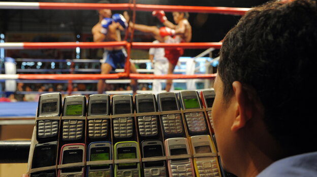 A Cambodian gambler talks on 18 cellphones at once at a boxing match in Phnom Penh in 2010. There are nearly 132 cellphones for every 100 Cambodians, but the country has also seen a surge in t