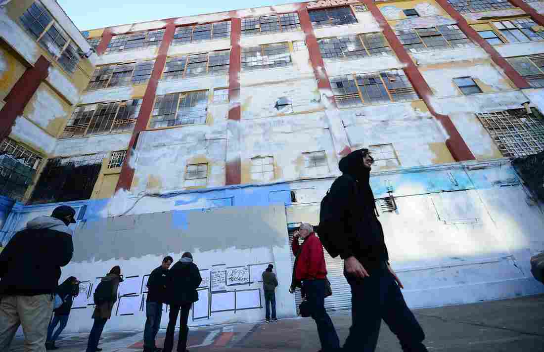 """People walk in front of New York's graffiti iconic spot """"5Pointz,"""" after the building was painted white in New York."""