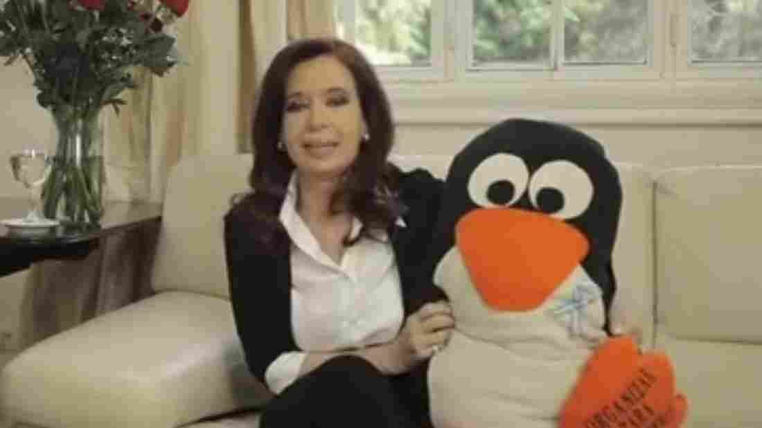 In this frame grab from a video released by Argentina's presidency, Argentina's President Cristina Fernandez holds a gift from a supporter given to her while recovering from surgery. She returned to work Monday, meeting with Cabinet ministers and recording a video that showed her in good spirits weeks after surgery to drain blood from inside her skull.