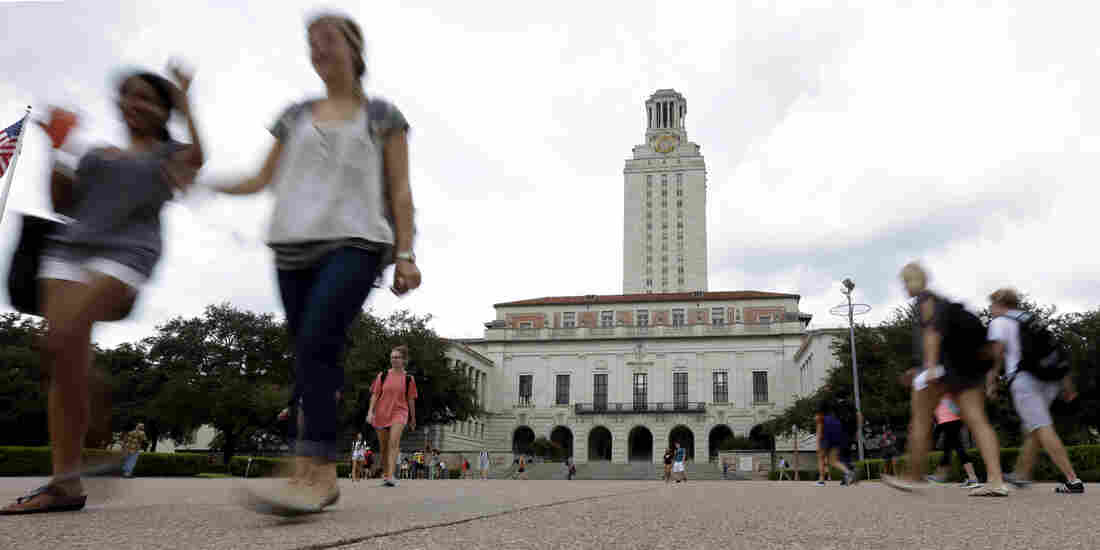 Students walk through the University of Texas at Austin campus near the school's iconic tower in Austin, Texas.