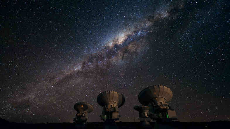 Part of the ALMA array on the Chajnantor plateau of Chile points skyward to the Milky Way, our own galaxy. The center of our galaxy is visible as a yellowish bulge crossed by dark lanes, which are themselves huge clouds of interstellar dust.