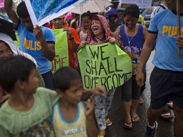 Some people marched in the rain Tuesday in the Philippine city of Tacloban, which was crushed by Typhoon Haiyan.