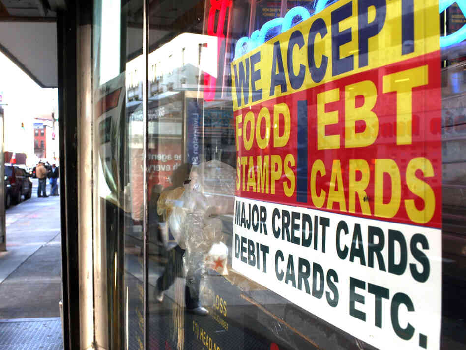 A sign in a New York City market window advertises the acceptance of food stamps.
