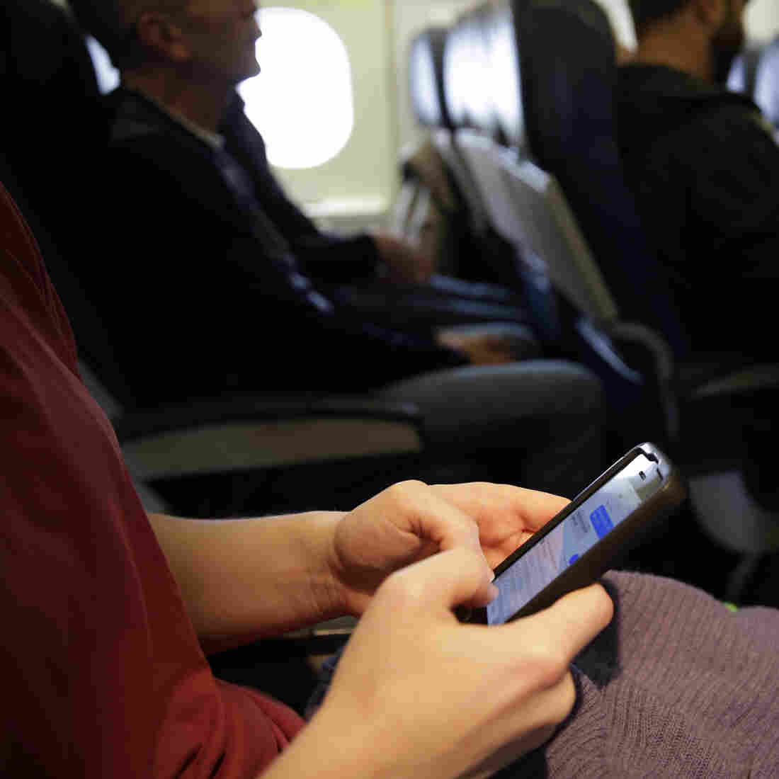 The new head of the Federal Communications Commission proposes allowing airline passengers to make phone calls during flights. Here, a passenger looks at her cellphone before a flight last month.