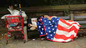 A homeless man sleeps under an American flag blanket on a park bench in New York City. New U.S. data reports a drop in the number of homeless people — but not in New York and other states.