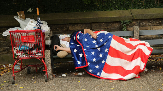 A homeless man sleeps under an American flag blanket on a park bench in New York City. New U.S. data reports a drop in th
