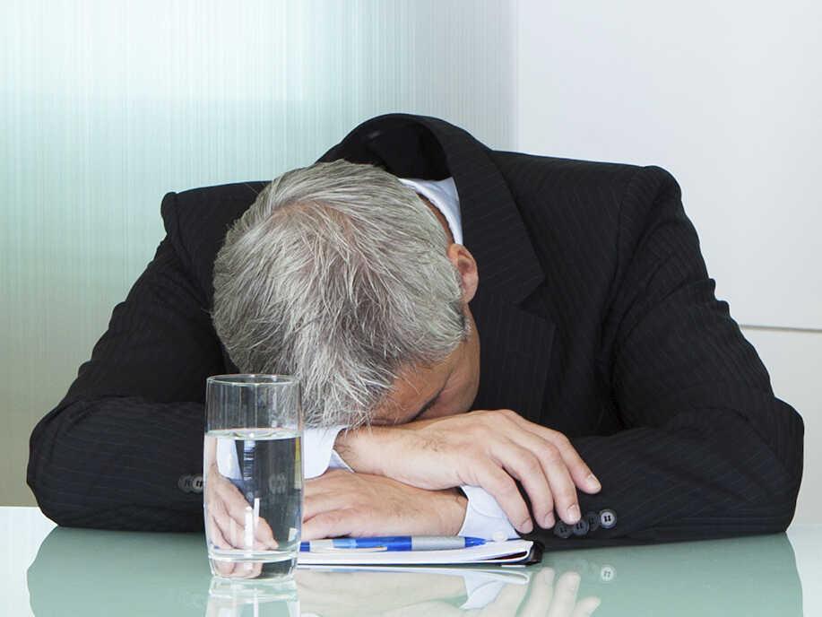 A bored man slumps on a table.