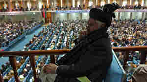 A member of the Afghan Loya Jirga listens as the more than 2,000 elders begin debating a proposed U.S.-Afghan security pact on Thursday in Kabul.