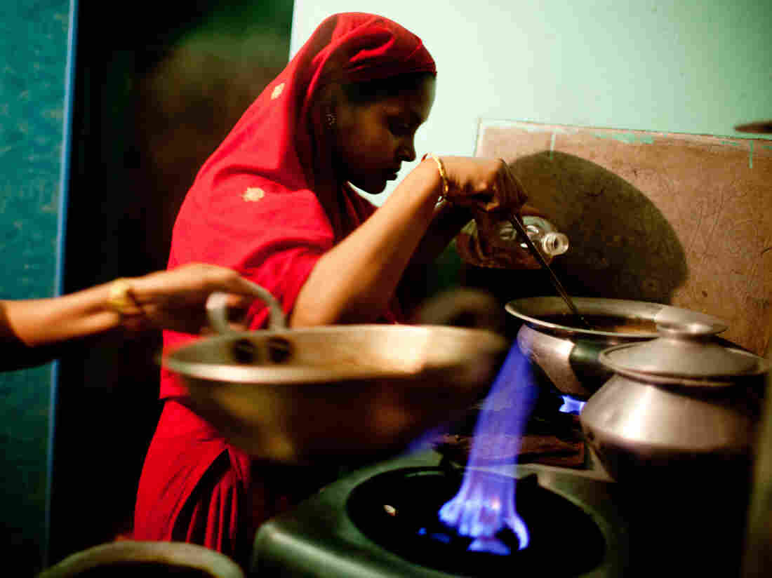 Minu cooks on the two shared burners outside her room in the city.