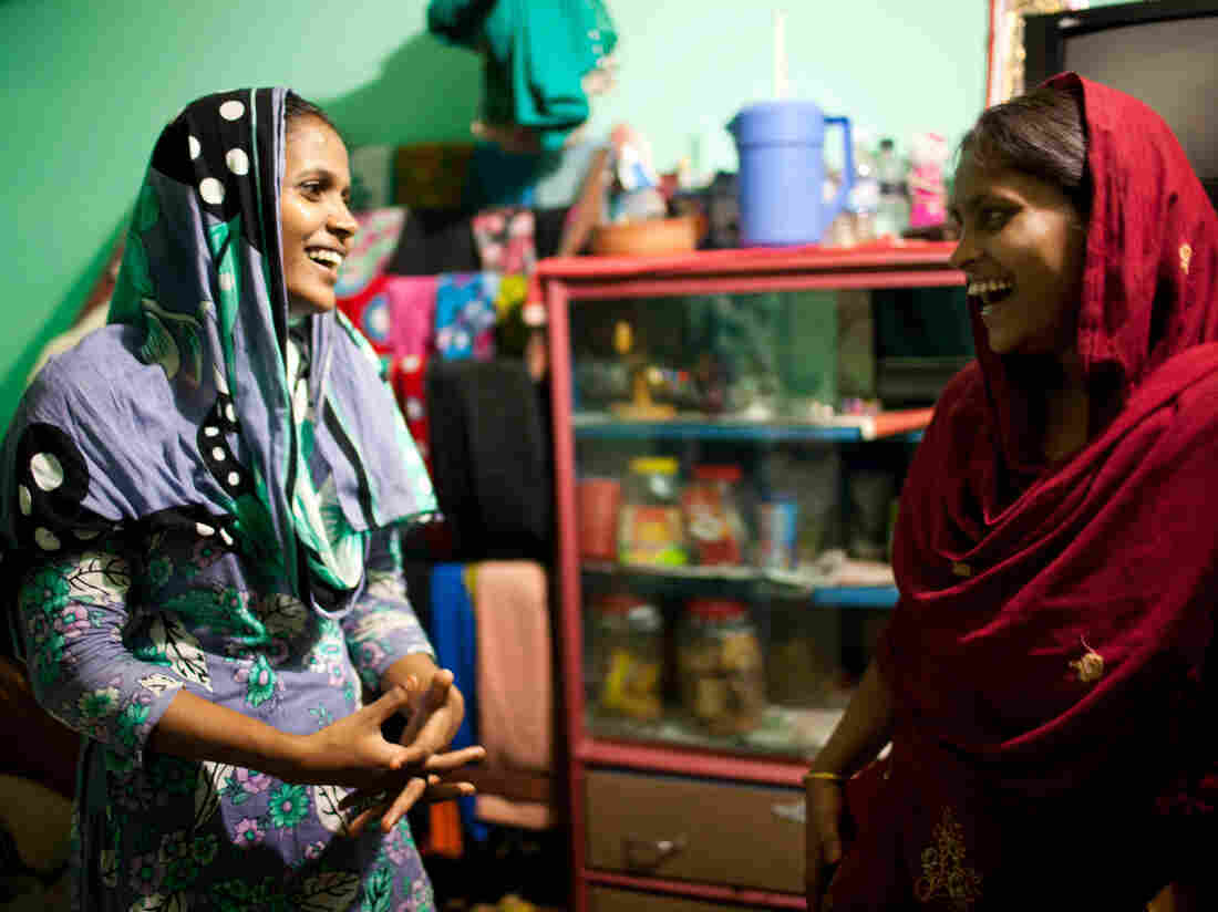 Shumi, left, and Minu, right, inside the small room they share with Minu's husband.