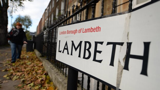 A pedestrian walks along Lambeth Road in south London on Friday. Police have rescued three women from a home in the neighborhood. They were held hostage for some 30 years, according to authorities.
