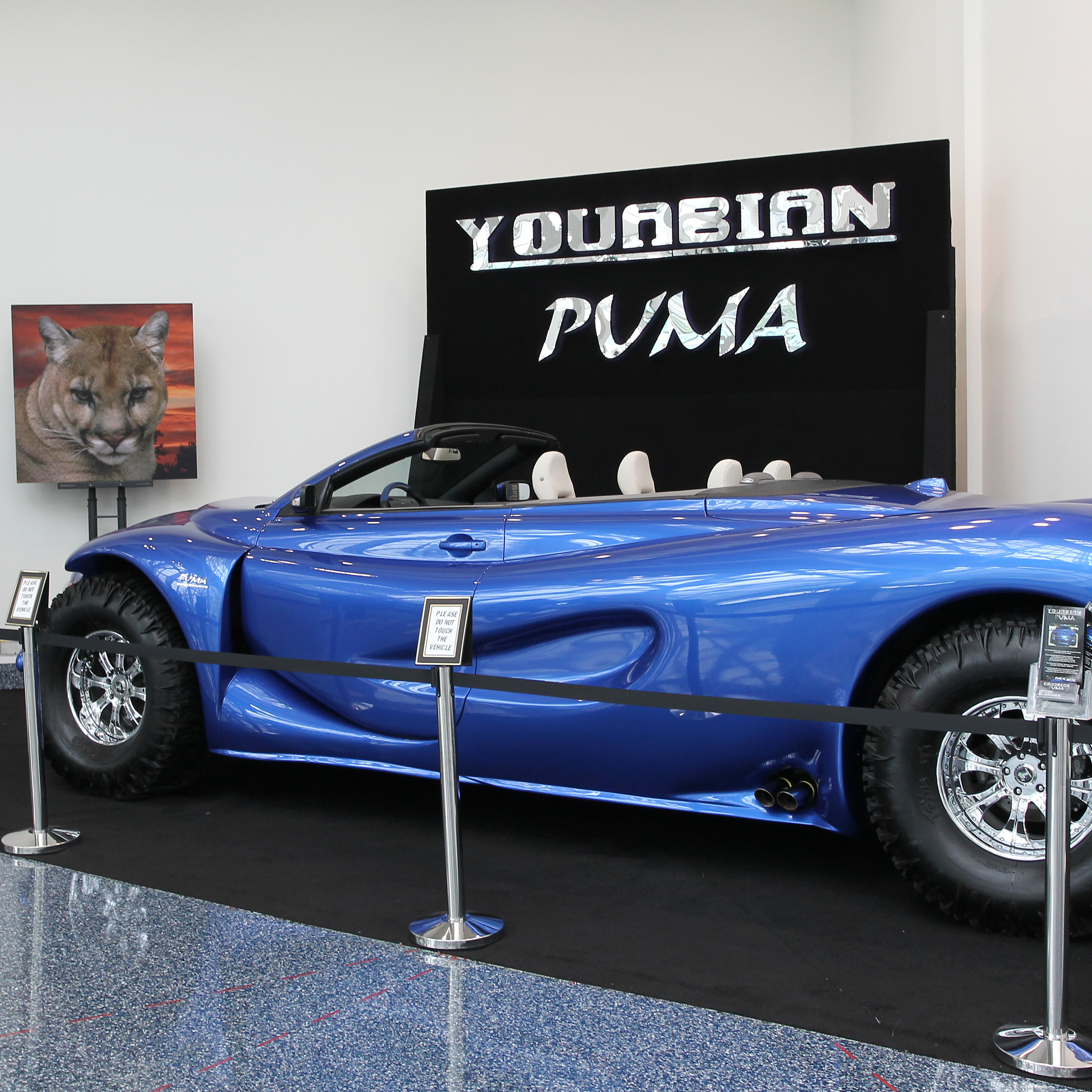 "The Youabian Puma, a 20-foot convertible that sits on 44-inch tires, has been panned by auto industry critics at the LA Auto Show. Some call it ""insane."" Other say they hope it's just a joke."
