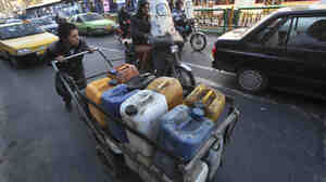 A man pushes his cart loaded with fuel containers in Tehran, Iran. Sanctions on Iran's oil have put a serious dent in the country's economy, pushing up the inflation rate to 40 percent.
