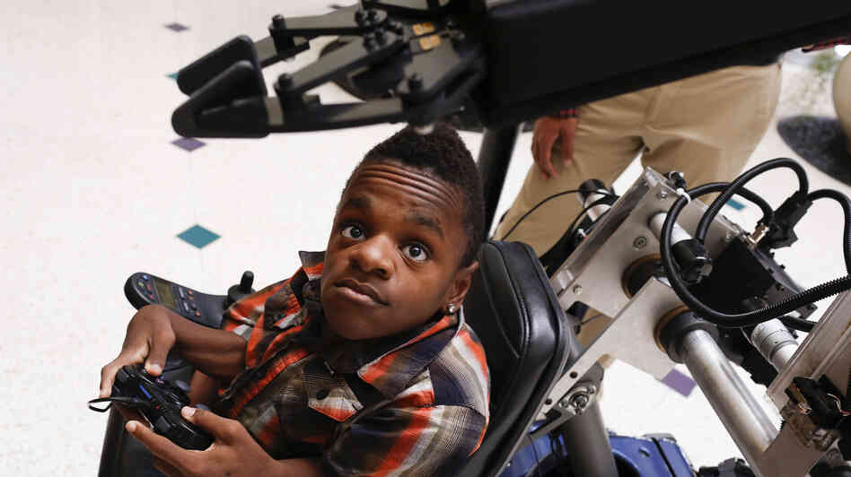 Dee Faught tests a robotic arm installed on his wheelchair in September. Commercially produced robotic a