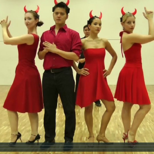 "A still image of dancers in Andres Florez' video titled ""The Super-Hero Salsa: Understanding the Role of MYCN in Neuroblastoma using a Systems Biology Approach. (Dance your PhD 2013)."""