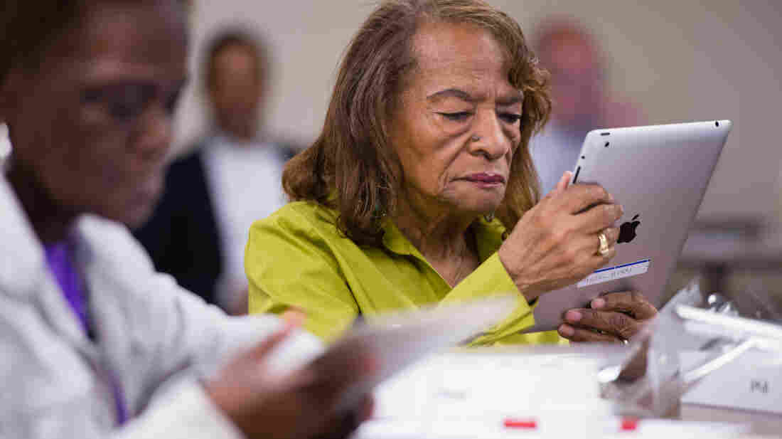 Hazel Avery, 86, holds her iPad for the first time. The Connecting to Community program, with funding from the AARP Foundation, te