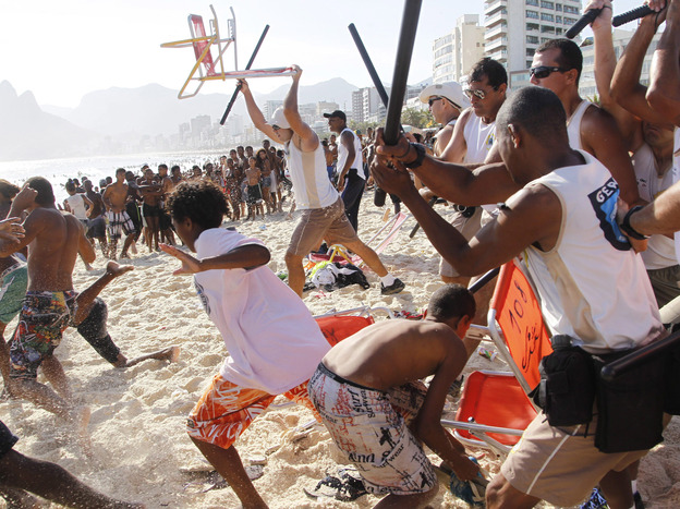 Municipal guards with batons chase a mob of thieves that snatched bags and wallets from beachgoers on Arpoador beach, adjacent to Ipanema, in Rio de Janeiro on Nov. 20.