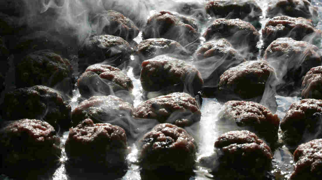 Moose patties sweetened with blueberries cook on the grill before the start of the Wild Game Supper.
