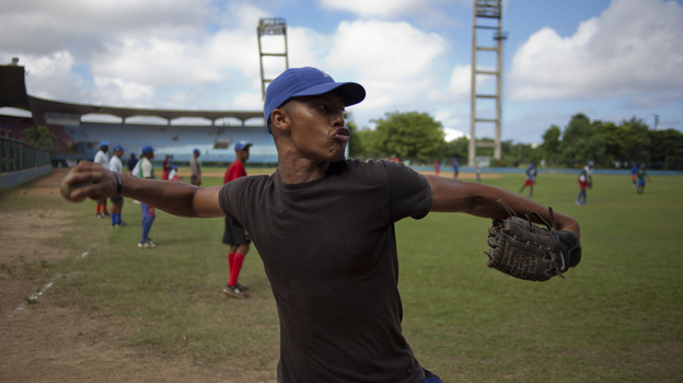 A player for Havana's Industriales baseball team winds up to throw a ball during a training session in Havana on Sept. 27. Cuba recently lifted a ban on its athletes' signing contracts to play overseas professionally. (AP)