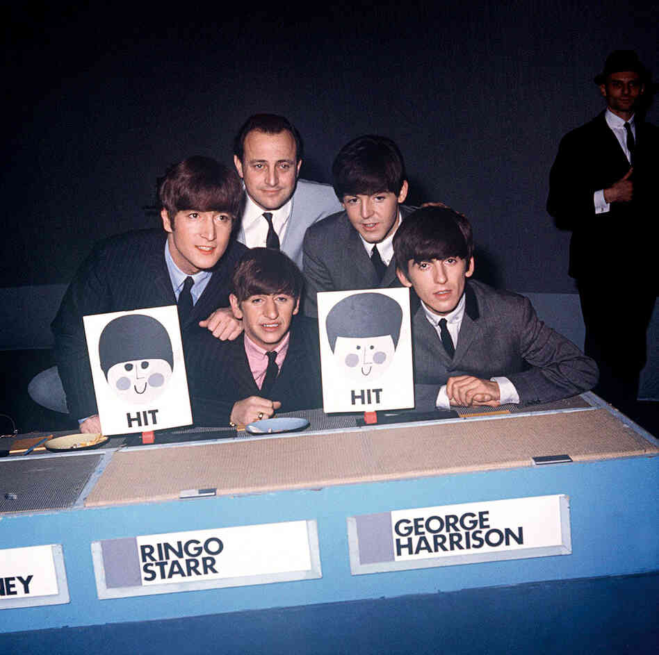 Posing with manager Brian Epstein, The Beatles appear on the BBC1 music panel show Juke Box Jury on Dec. 7, 1963.