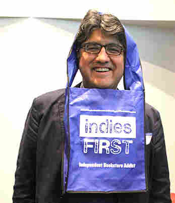 Sherman Alexie models an Indies First tote bag.  He plans to put in shifts at five Seattle bookstores this Saturday.