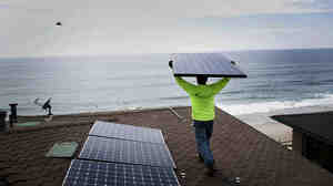 Andres Quiroz, an installer for Stellar Solar, carries a solar panel during installation at a home in Encinitas, Calif.