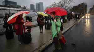 Passengers wait for a BoltBus to arrive during a light rain, Wednesday, Nov. 27 in New York. A wall of storms packing ice, sleet and rain could upend holiday travel plans as millions of Americans take to the roads, skies and rails for Thanksgiving.