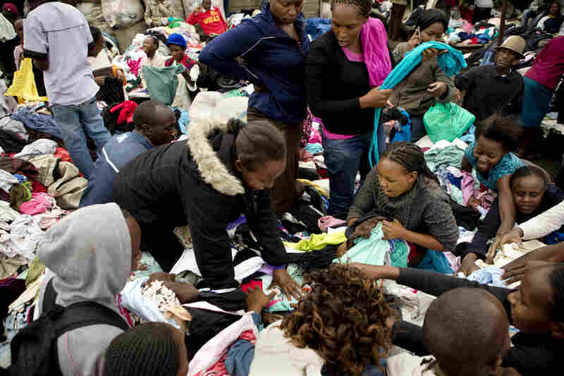 Customers scramble to grab T-shirts as a bale is opened at Gikombo Market. Some people are shopping for themselves, while others will wash, mend and iron the clothes and sell them for a higher price to earn a living.