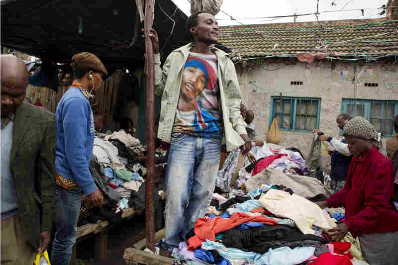 A T-shirt vendor at Gikombo Market wears a shirt he bought from the market.