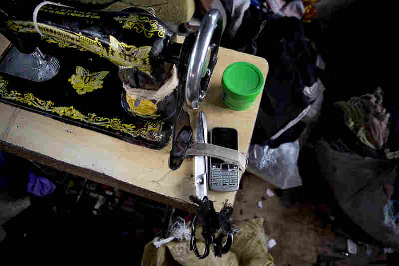 A tailor shop above Gikombo Market handles repairs and alterations of T-shirts and clothes from the market. Scissors and a mobile phone are tied down next to a sewing machine at the shop.